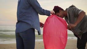 照亮红色纸灯的年轻不同种族的夫妇在发射前 在海滩的浪漫日期 可爱的妇女 影视素材
