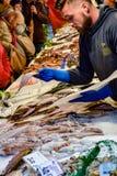 照应顾客的年轻白种人男性鱼市工作者在威尼斯大石桥市场,威尼斯,意大利上 免版税库存照片