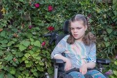 照料一名义务关心工作者轮椅的一个残疾儿童 免版税库存图片