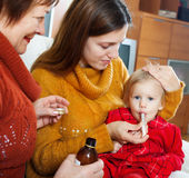 照料不适的婴孩的两名妇女 免版税库存图片