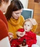 照料不适的婴孩的两名妇女 免版税图库摄影