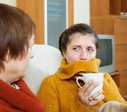 照料她的成人女儿的妇女得寒冷 免版税图库摄影