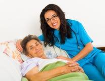 照料更老的患者的护士 免版税库存图片