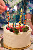 照明设备在一块白蛋糕的生日蜡烛,装饰用草莓和莓果 免版税库存图片