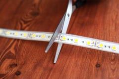 照明设备的设施的硅树脂LED小条在房子里 剪刀削减了额外pieceribbons 免版税库存图片
