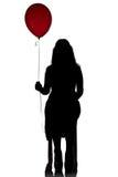 照片与红色气球的坐的妇女的剪影 库存照片