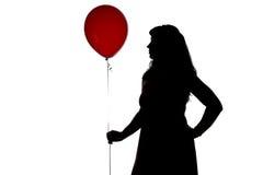 照片与红色气球,外形的妇女的剪影 免版税库存图片