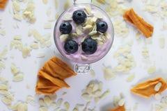 照片从上面蓝莓酸奶用在上面,杏仁和干燥芒果装饰的蔓越桔 库存图片