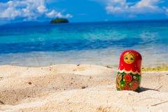照片俄国玩偶Matrioshka纪念品未触动过的热带海滩在巴厘岛 水平的照片 被弄脏的背景 免版税图库摄影