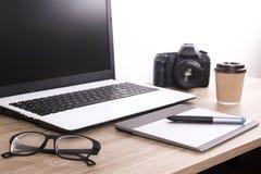 照片博客作者/摄影师/它与膝上型计算机、黑屏、咖啡杯和电子的专家` s典型的办公室空间桌 库存图片