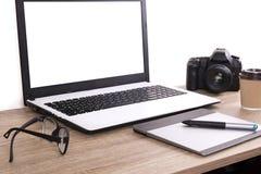 照片博客作者/摄影师/它与膝上型计算机、黑屏、咖啡杯和电子的专家` s典型的办公室空间桌 图库摄影