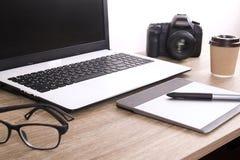 照片博客作者/摄影师/它与膝上型计算机、黑屏、咖啡杯和电子的专家` s典型的办公室空间桌 免版税库存照片