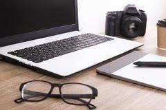 照片博客作者/摄影师/它与膝上型计算机、黑屏、咖啡杯和电子的专家` s典型的办公室空间桌 免版税库存图片