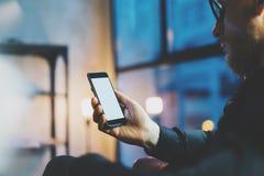 照片商人松弛现代顶楼办公室 人坐的椅子夜 使用当代智能手机,被弄脏的背景 免版税库存照片