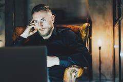 照片商人松弛现代顶楼办公室 坐在葡萄酒椅子的人在晚上 使用contemporarylaptop,被弄脏 免版税库存照片