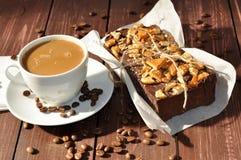 照片在一张土气纸和杯子装饰用饼干小片断和安置的包裹一个开胃巧克力蛋糕 免版税图库摄影