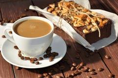 照片在一张土气纸和杯子装饰用饼干小片断和安置的包裹一个开胃巧克力蛋糕 图库摄影