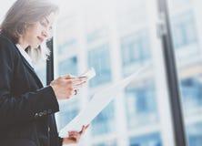 照片女商人佩带的衣服,看智能手机和在手上拿着文件 露天场所顶楼办公室 全景窗口ba 库存图片