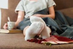 照片妇女与杯牛奶软休息的格子花呢披肩的沙发床 库存图片