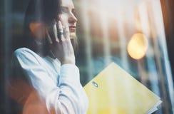 照片妇女佩带的白色衬衣,谈的智能手机和举行事务在手上归档 露天场所顶楼办公室 全景视窗 免版税库存图片