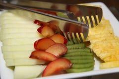 照片方形的白色瓷盘用切好的成熟异乎寻常的果子和莓果:猕猴桃,瓜,菠萝,红色李子 库存图片