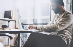 照片有胡子的图表设计师与新的项目现代顶楼一起使用 在木桌上的普通设计笔记本 anatolian 免版税库存照片