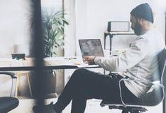 照片有胡子的图表经理与新的项目现代顶楼一起使用 使用在木桌上的contemprary膝上型计算机 创造性 库存照片