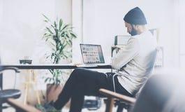 照片有胡子的帐户主任与新的项目现代演播室一起使用 使用在木桌上的contemprary笔记本 库存图片