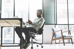 照片有胡子的年轻人与新的项目现代露天场所顶楼一起使用 使用contemprary手机手 创造性 免版税库存图片