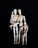 照片木玩偶,有孩子的愉快的家庭黑背景的 免版税库存图片