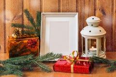 照片框架、灯笼和圣诞节礼物在木桌上 库存图片