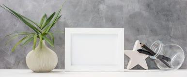 照片框架关闭嘲笑与在花瓶、陶瓷星、笔和铅笔的棕榈叶在架子的金属螺盖玻璃瓶 斯堪的纳维亚样式 免版税图库摄影