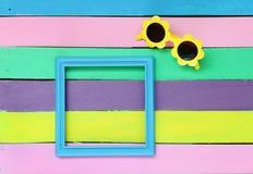 照片框架和太阳镜在五颜六色的木背景 免版税图库摄影