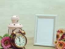 照片框架和蜡烛光和闹钟和人造花 免版税库存图片