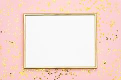 照片框架嘲笑与文本的,在桃红色背景的金黄衣服饰物之小金属片五彩纸屑空间 平的位置,顶视图 华伦泰` s 免版税库存照片