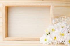 照片框架选择聚焦与花的在木桌上 免版税库存照片