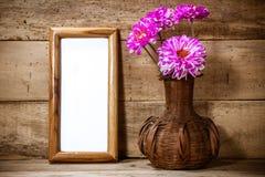 照片框架,在花瓶的美丽的桃红色花在木背景 库存图片