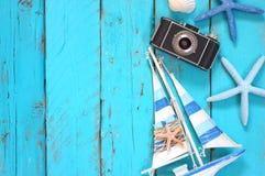 照片照相机的顶视图图象,木小船、海壳和星钓鱼在木桌 库存图片