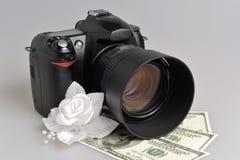 照片照相机,与金钱的婚姻的钮扣眼上插的花在灰色 图库摄影