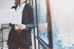 照片穿着现代衣服和在手上的女商人拿着纸 露天场所顶楼办公室 全景窗口背景 horizo 库存照片