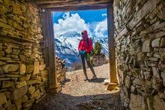 照片美好的妇女旅客背包徒步旅行者山方式 看起来的女孩去采取休息晴朗的大阳台 美丽的目的地横向滑雪雪 免版税库存照片