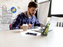 照片年轻人和talente提供经费给经理与新的项目一起使用 工作从他的家庭办公室的英俊的人 anatolian 免版税库存图片