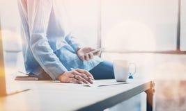 照片年轻女商人与新的起始的项目一起使用在现代coworking的办公室 坐的木桌,举行 图库摄影