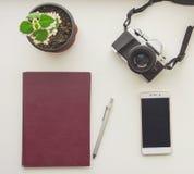 照相机、伯根地笔记薄、笔、绿色花和流动聪明的电话视图从上面 库存照片