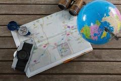照相机、双筒望远镜、地球、地图和指南针在木板条 库存图片