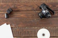 照相机、影片、纸和cd在木桌上 库存图片