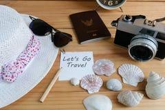 照相机、护照、太阳镜、帽子、壳和消息让` s去在木地板上的旅行 免版税库存图片