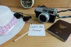 照相机、护照、太阳镜、帽子、壳和消息让` s去在木地板上的旅行 免版税库存照片