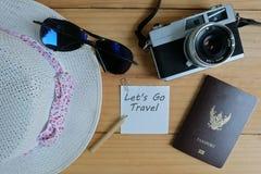 照相机、护照、太阳镜、帽子、壳和消息让` s去在木地板上的旅行 免版税图库摄影