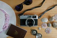 照相机、护照、太阳镜、帽子、壳和消息让` s去在木地板上的旅行 图库摄影